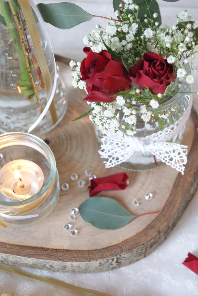 Glas mit Schleife, roten Rosen, Schleierkraut und Eukalyptusgrün