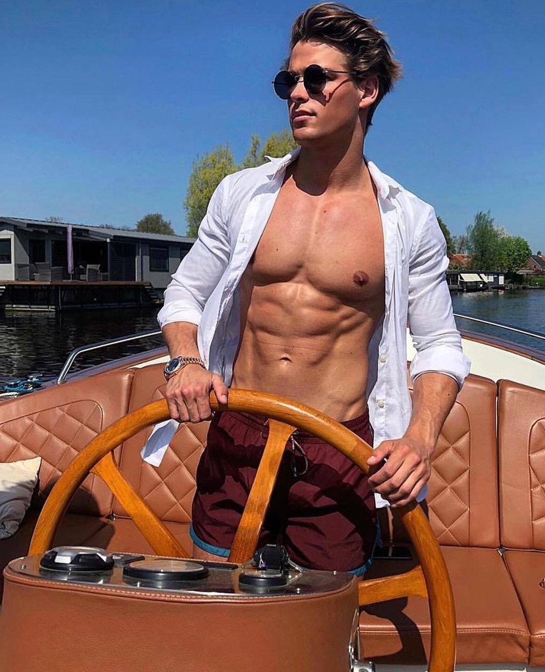 handsome-shirtless-fit-muscle-pecs-abs-hunk-young-male-model-sunglasses-thom-strijd-boat-driving