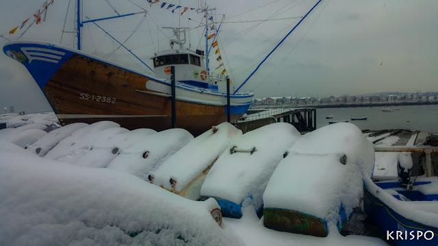 barco dr madera de hondarribia y barquitos tras una gran nevada