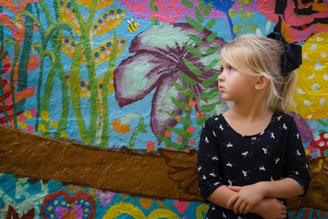 Pieni tyttö värikästä seinää vasten