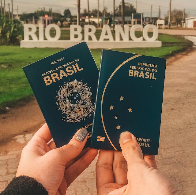 Mãos segurando passaportes em frente do letreiro de Rio Branco