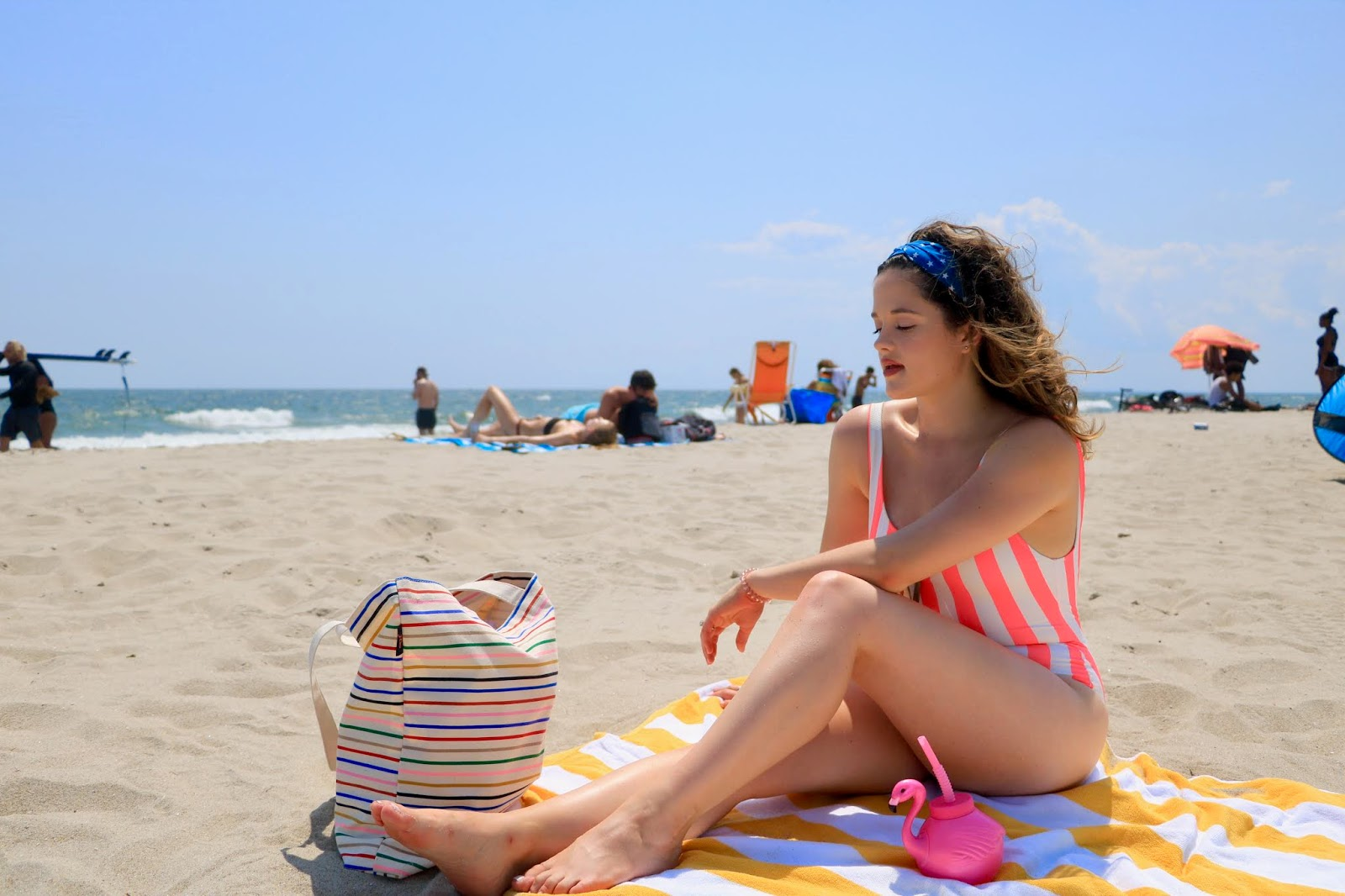 Nyc fashion blogger Kathleen Harper on the beach with her striped swimsuit, striped beach bag, and striped towel.