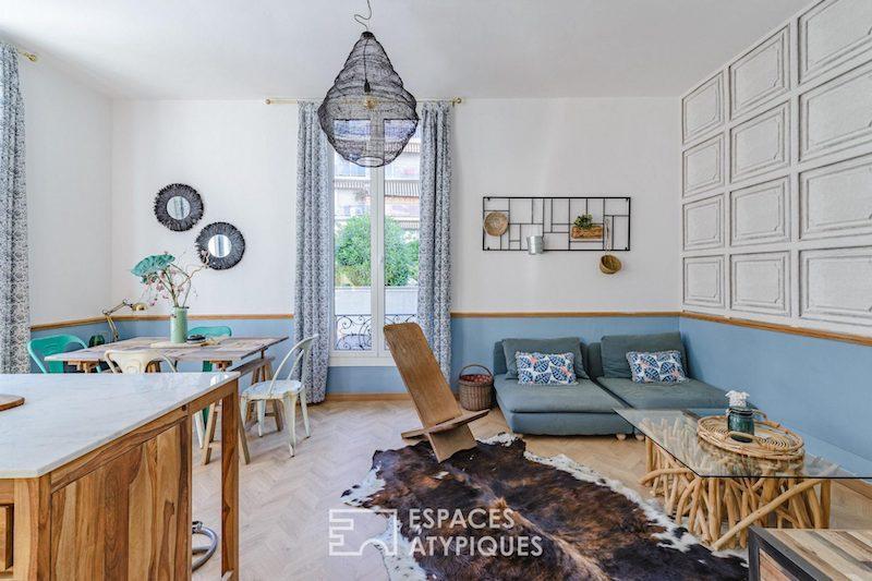 Salón abierto a la cocina moderno y funcional con medias paredes pintadas.