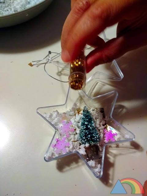 Rellenando estrella navideña con nieve de porexpán y purpurina
