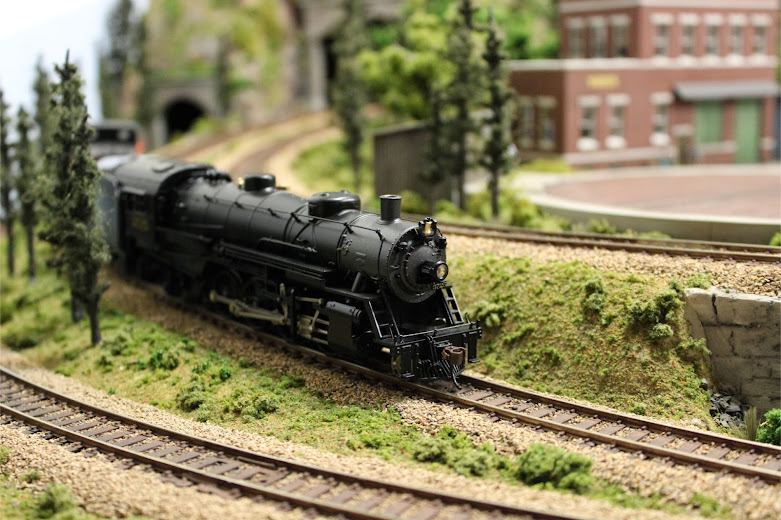 A USRA Light Mikado 2-8-2 steam locomotive descending down a gentle incline in a mountain forest scene
