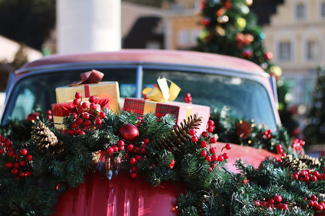 car decorated with Christmas wreath Photo by Honey Fangs on Unsplash