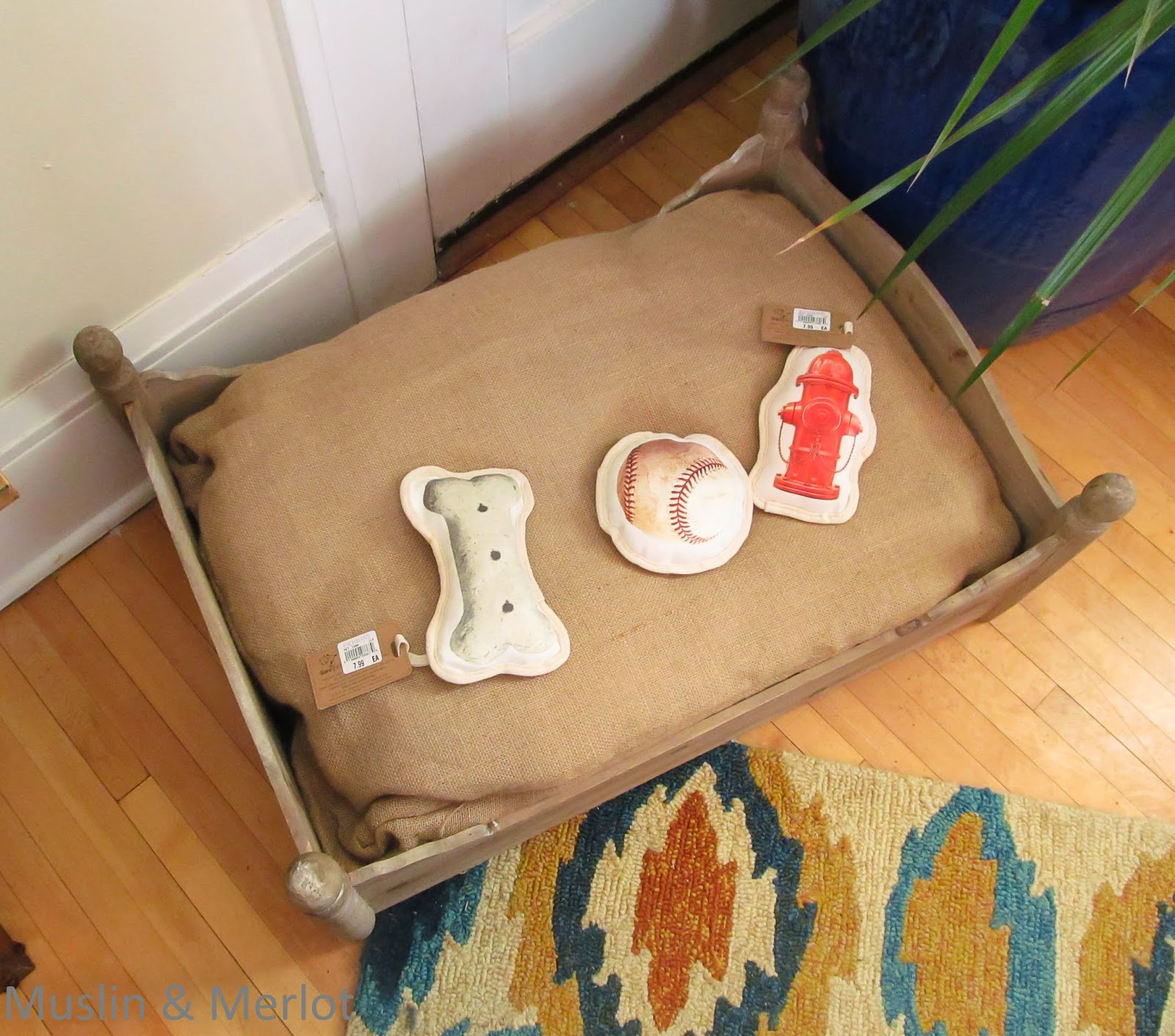 Cute dog bed with stair finials at the corners to mimic the look of a four poster bed.