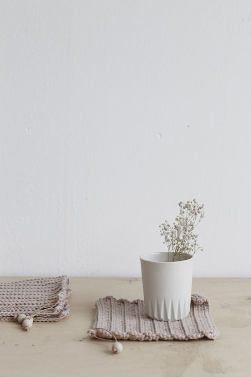 Beautiful simple stoneware cup upon handknit coaster - found on Hello Lovely Studio