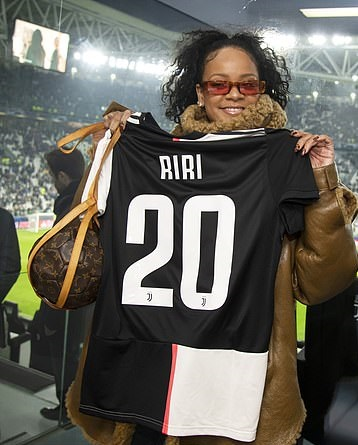 Rihanna looks every inch the footie fan as she holds up a personalised 'RiRi' shirt (photos)