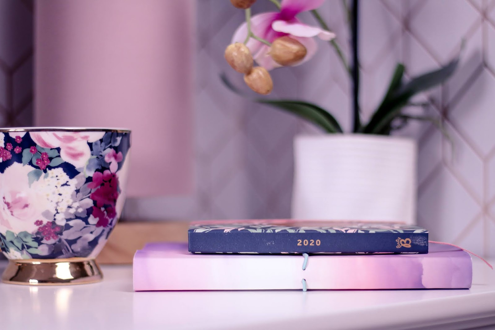 Close up photo of a 2020 diary on a pink and purple notebook and a flower tea cup on top on a white side table with a pink lamp and faux pink orchid in the background blurred.
