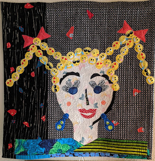 Fabric collage of girl's face with emoji fabric cut as pigtails
