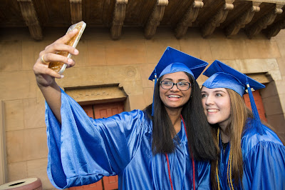 photo of two students in caps and gowns taking a selfie
