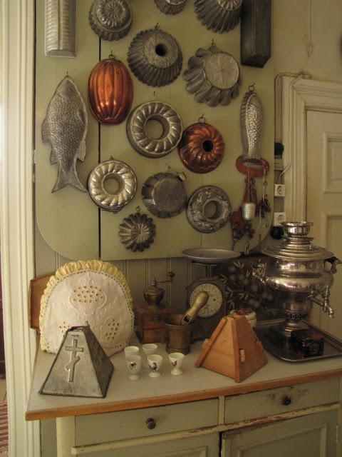 Seinällä metallisia ruokamuotteja ja pöydällä pasha-muotteja.