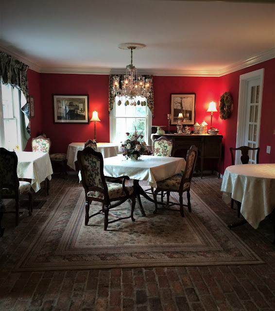 multi-tabled dining room with cranberry-colored walls