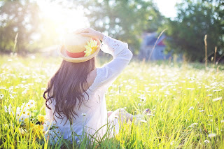 blog picture of lady sitting in field with flowers and the sun shining