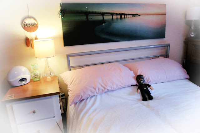 A double bed with white duvet and pink pillows, above it, a landscape photograph of a pier, to the side a bedside table with a lamp, Lumie Bodyclock and painted carafe. There's a dreamcatcher above it on the wall. In the middle of the bed is a stuffed Starlord figure.
