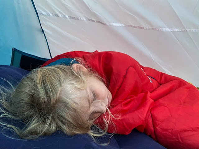 A young girl in a sleeping bag in a tent asleep