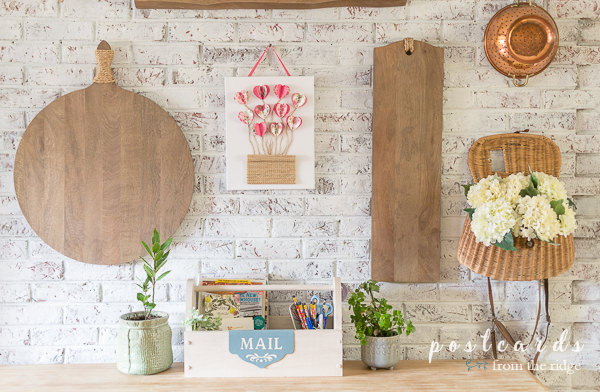 white brick wall with wood cutting boards and 3-d paper heart wall art