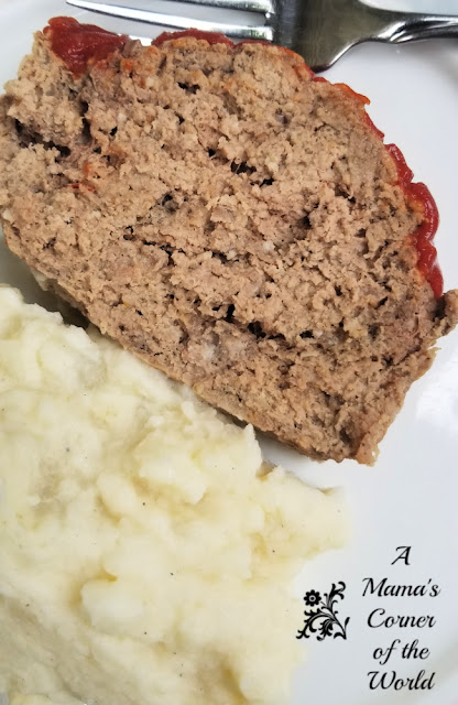 Meatloaf, mashed potatoes and a fork on a white plate.