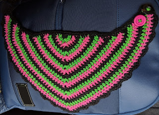 Crochet bib in pink, green and black, with a frilly black border.