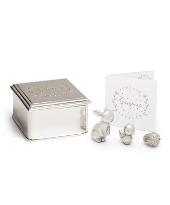 A small metal box next to metal figures of a rabbit, bird and acorn