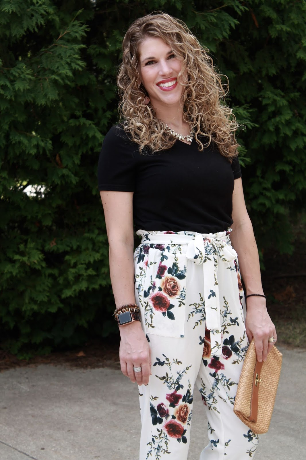 white floral paper bag pants, black tee, straw clutch, burgundy heels
