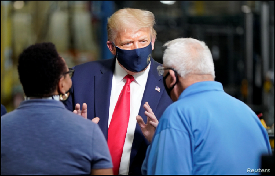 El presidente Donald Trump conversa con dos trabajadores en una planta de producción de la compañía Whirlpool en Clyde, Ohio, el jueves 6 de agosto de 2020 / REUTERS