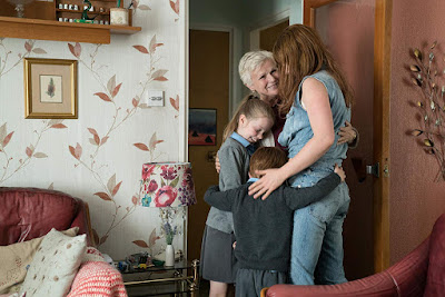 "Julie Walters embraces Jessie Buckley, Daisy Littlefield, and Adam Mitchell in ""Wild Rose"" (2019)."