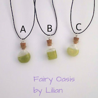 On a white back ground  lay three necklaces with glass bottles filled with sparkly green material.  Text reads Fairy Oasis by Lilian