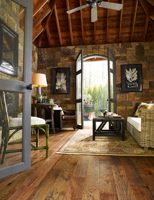 Rustic family room with hardwood flooring and stone walls