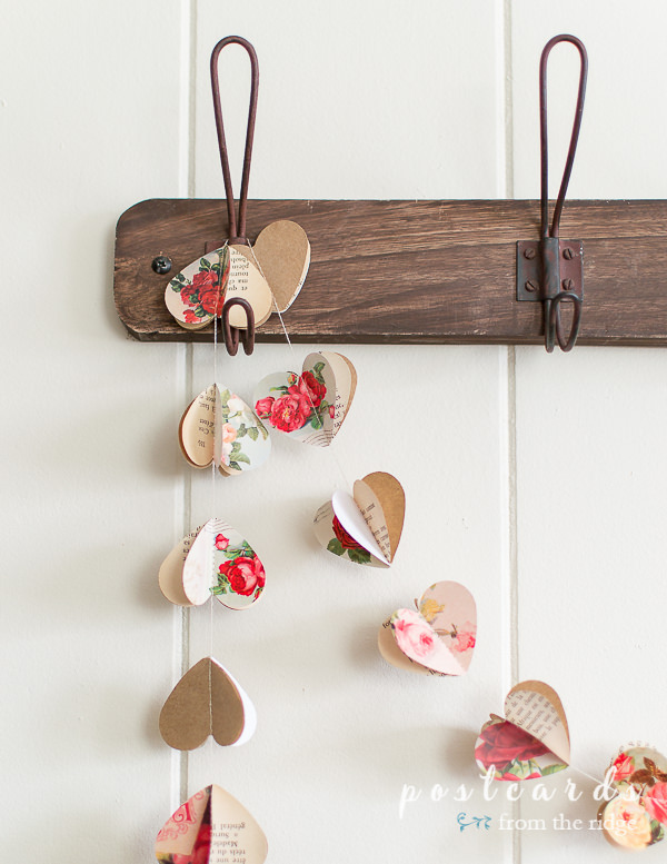 vintage paper heart garland hanging from wood rack with wire hooks
