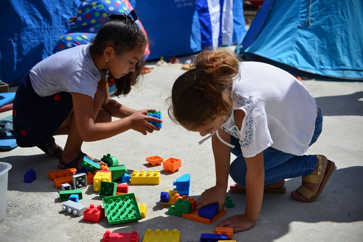 Girls playing with plastic building blocks that look like large lego pieces.