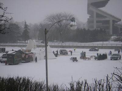 Skate patroller pushing a toboggan on the canal with Lansdowne Park/Frank Clair Stadium's south side stands in the background, 2009.