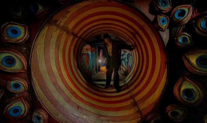 Imagem de capa: um túnel de parque de diversões com uma parede com olhos amarelos nas cores vermelhos e azuis e um túnel amarelo com espirais vermelhas e o personagem Bradley Cooper em um casaco e chapéu saindo do túnel com uma lanterna.
