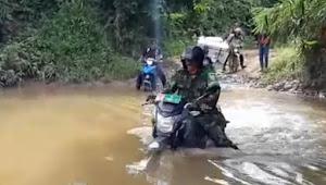 Sertu Umar Seberangi Sungai Pakai Motor Untuk Distribusikan Logistik Pemilu