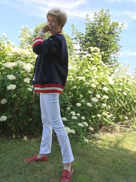 woman in white jeans, red loafers, and a navy, red and white baseball jacket, standing in front of white hydrangeas