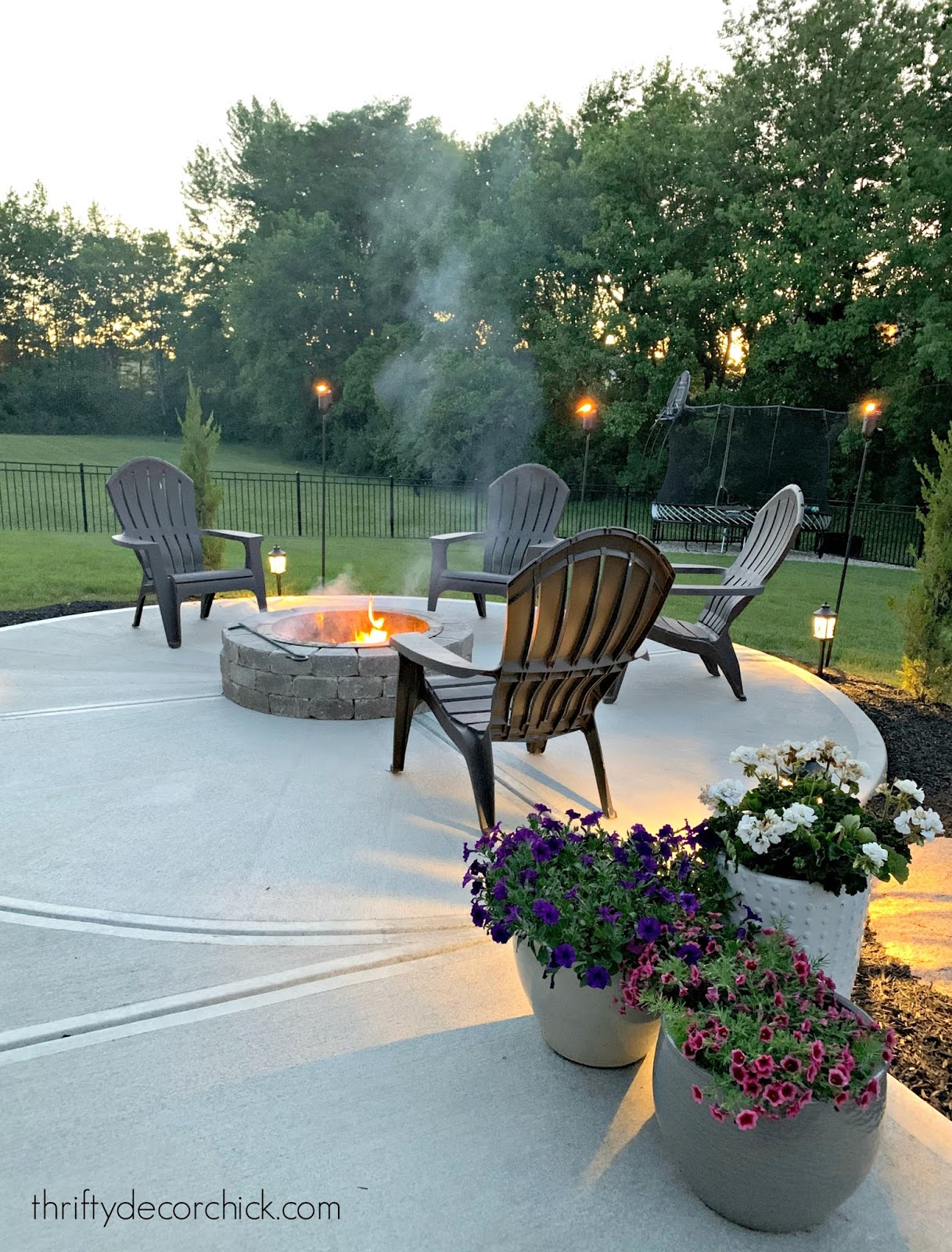 Concrete with round fire pit and chairs