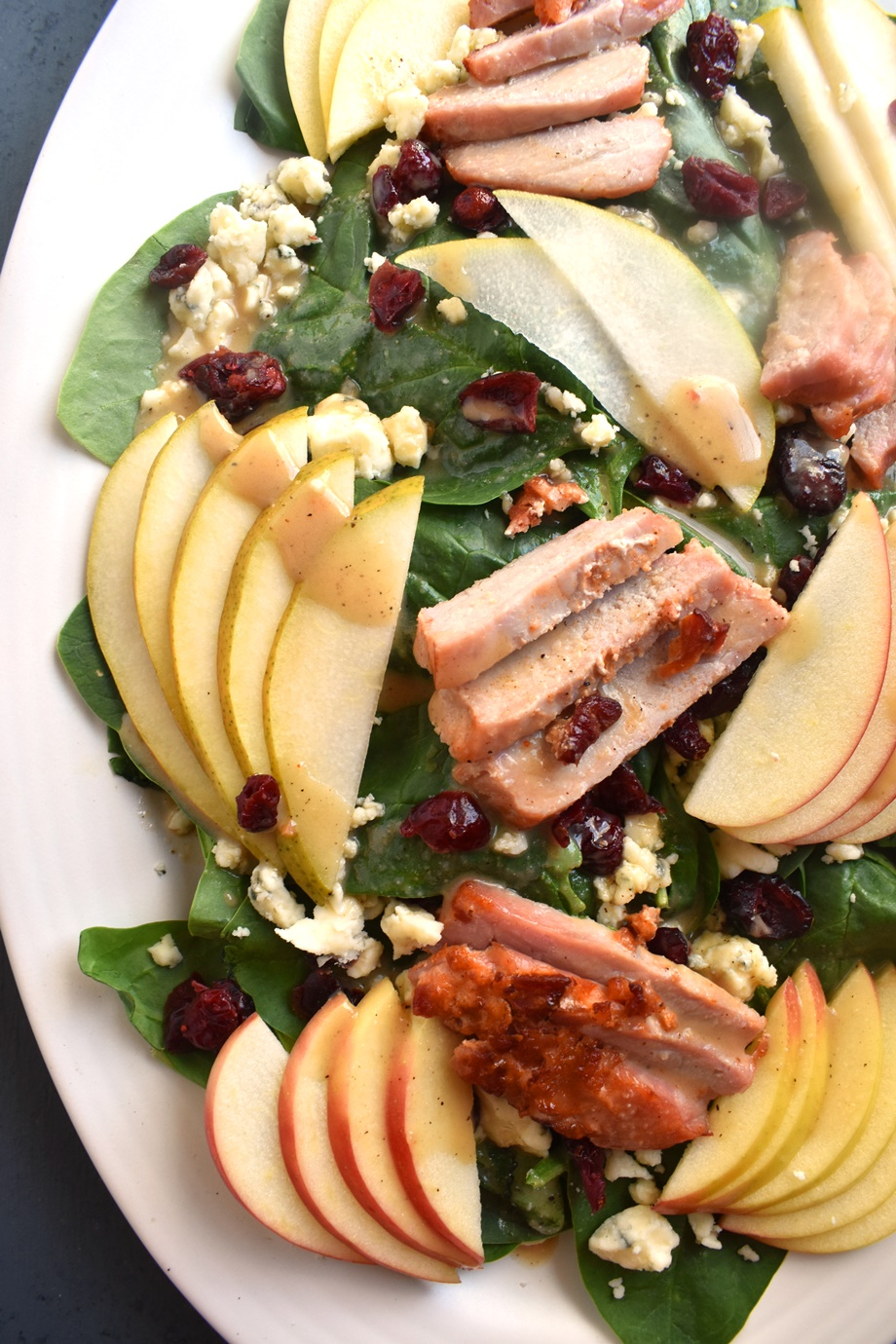 Loaded Pear and Apple Salad features sliced honeycrisp apples, pears, roasted pork tenderloin, cranberries, blue cheese and an easy dijon vinaigrette!