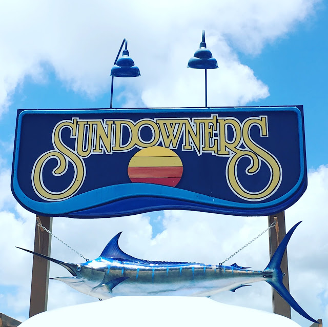 "The sign for Sundowners that you see in the parking lot. It shows a color blocked sun setting into the ocean. The background of the sign is blue and large yellow letters read, ""Sundowners."""