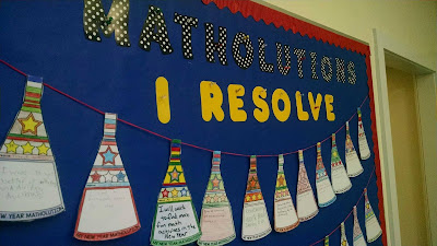 "Ms. Barnaby titles her matholution bulletin board ""Matholutions I RESOLVE""."