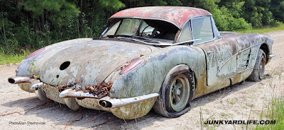Rear of 1959 Corvette sitting on dirt road after it was dug out of a field.