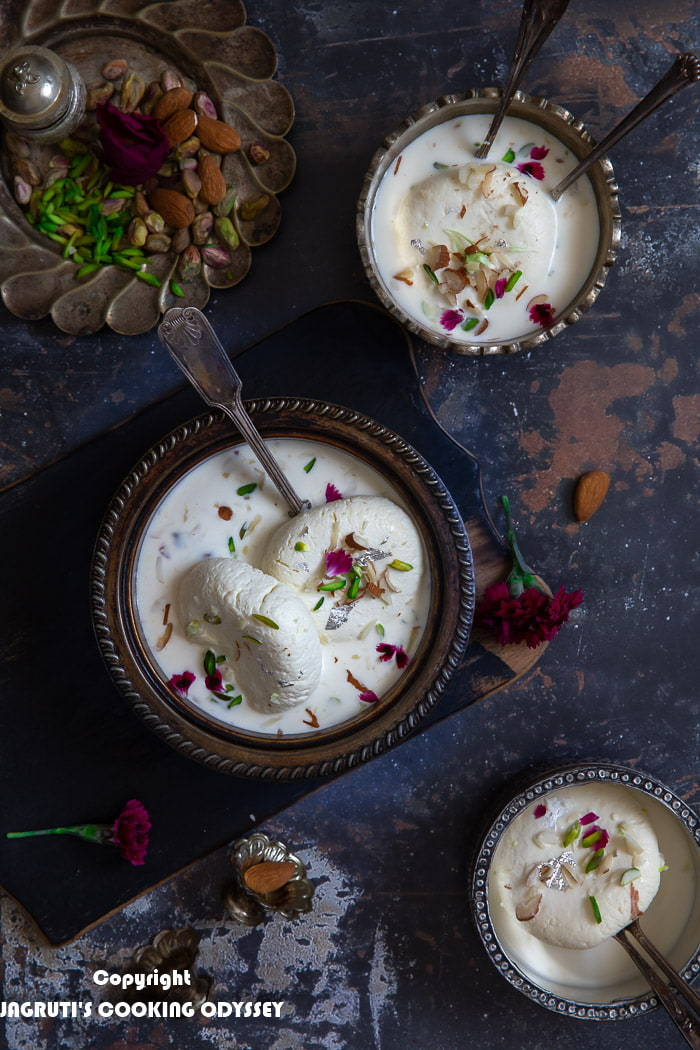 White ras malai served in a metal bowl with a spoon on black chopping board next to pistachio and almond bowl.