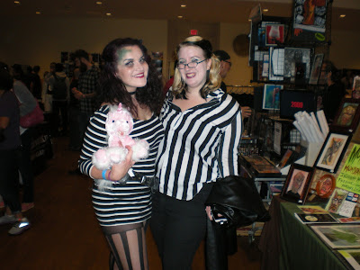 Two con attendees in black and white striped costumes, one with ghoulish green paint on her face and holding a stuffed unicorn.