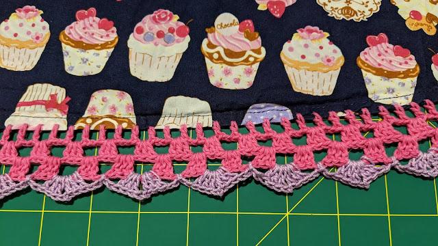 Cupcake fabric with hem of pink and purple crochet.