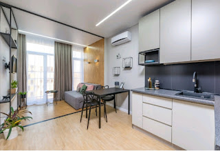 A studio apartment with a kitchen, dining room, and living room area.