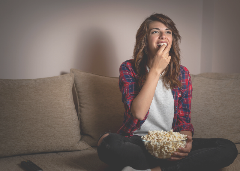 Lady watching TV in a post about 10 feel-good TV and films for a self-care night