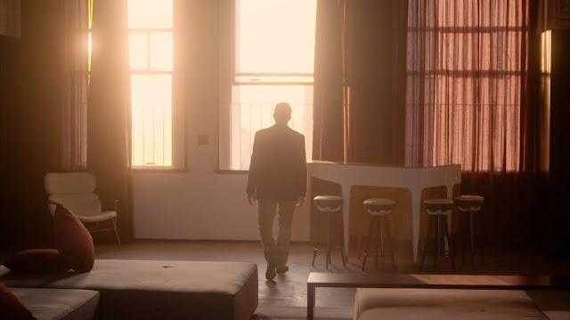 Homem caminha para ver o pôr do sol na janela