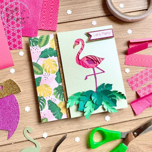 iris folded flamingo card surrounded by paper crafting supplies