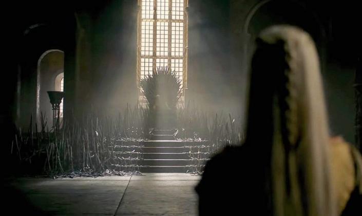 Imagem de capa: cena do trailer em que se vê uma mulher de cabelos platinados de costa em frente ao Trono de Ferro na sala do trono, uma cadeira feita de espadas derretidas e cercada de mil espadas pontudas.
