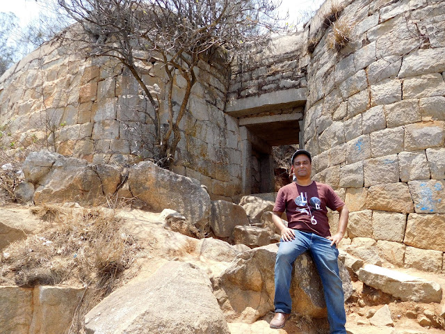 Sitting near the outer wall of the Nandidurg fort, Nandi Hills